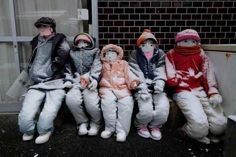 Bonecos de crianças enfileirados sentados