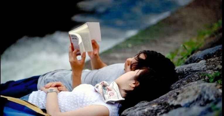 Casal de jovens deitados juntos lendo livro