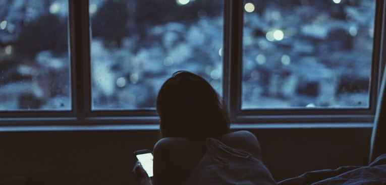 Adolescente olhando o celular ao entardecer