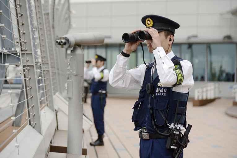 Policiais com binóculo vigiando o céu