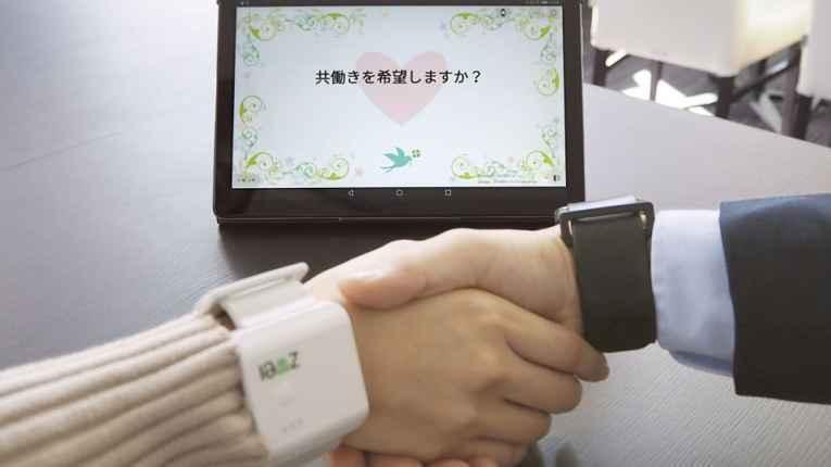 Pessoas apertando as mãos usando os relógios com AI