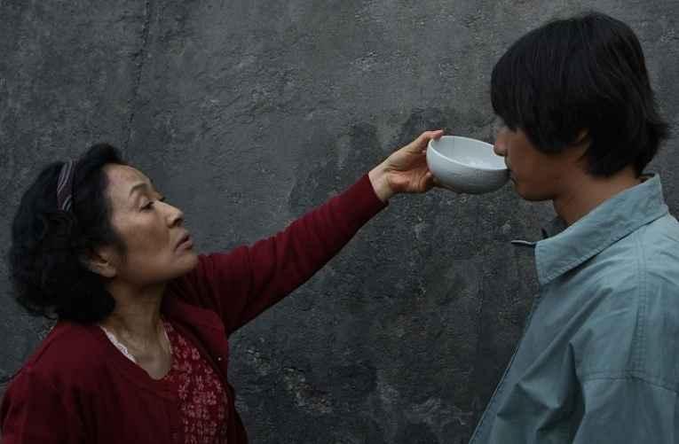 Mãe dando tigela para filho adulto beber