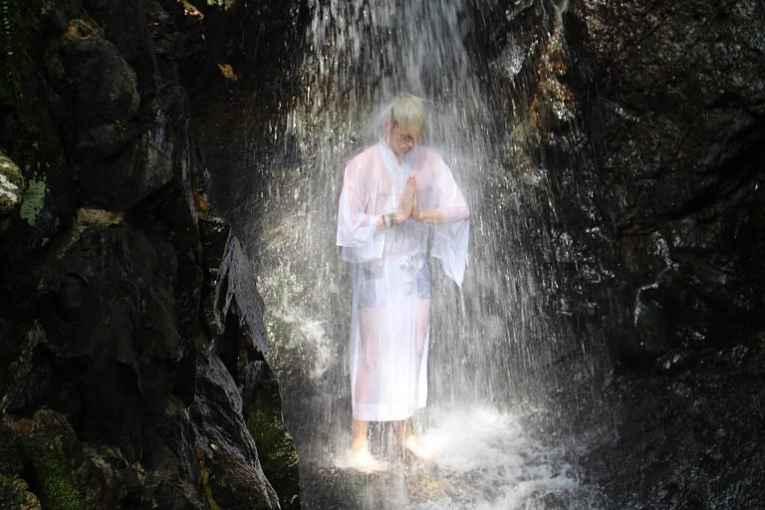Homem meditando embaixo da cachoeira