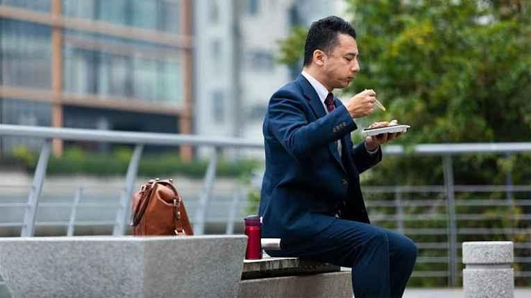 Homem almoçando na rua