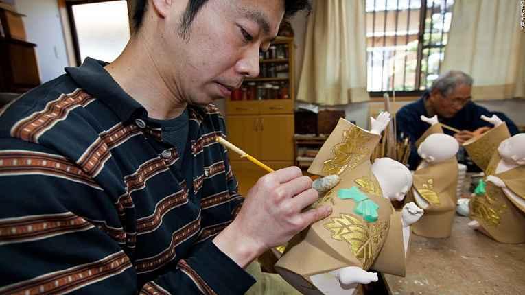 Artesão pintando detalhes da boneca Hakata