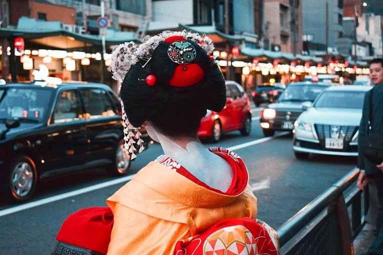 Geisha de costas em rua movimentada