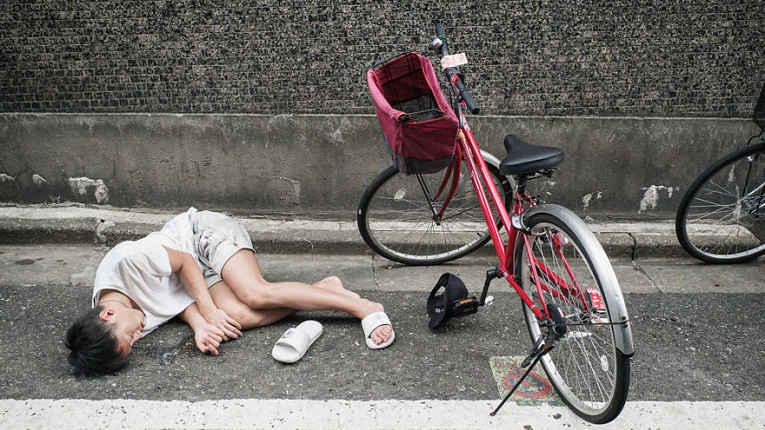 Homem caído ao lado da bicicleta