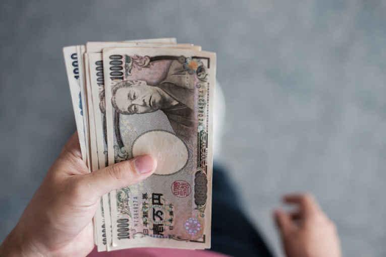 Mãos segurando notas de ienes