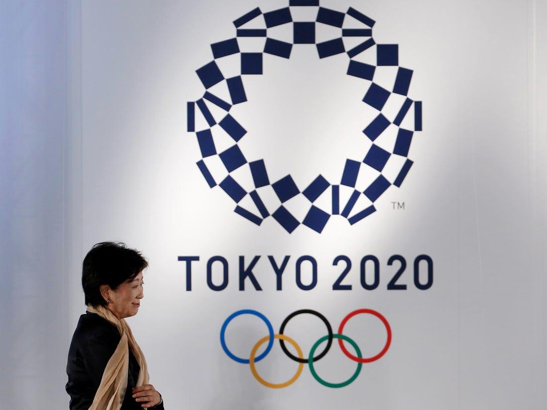 Mulher passando em frente ao logo das Olimpíadas no Japão